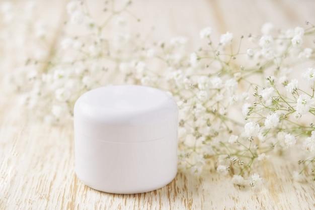 Prodotto per la cura della pelle crema cosmetica naturale in barattolo di plastica su uno sfondo di legno.