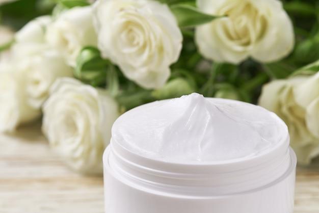 Crema cosmetica naturale con cura del viso a base di erbe o lozione idratante, primo piano. vaso di plastica bianco per crema per la pelle sensibile su un tavolo di legno.