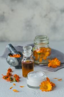 Olio cosmetico naturale, tintura o infuso, unguento, crema o balsamo e mortaio con fiori di calendula secchi e freschi su grigio