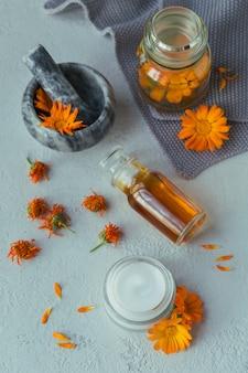 Olio cosmetico naturale, tintura o infuso, unguento, crema o balsamo e mortaio con fiori di calendula secchi e freschi.