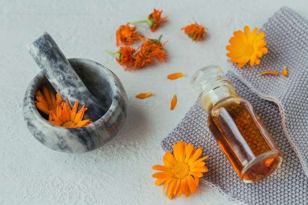 Olio cosmetico naturale, tintura o infuso e mortaio con fiori di calendula secchi e freschi su grigio