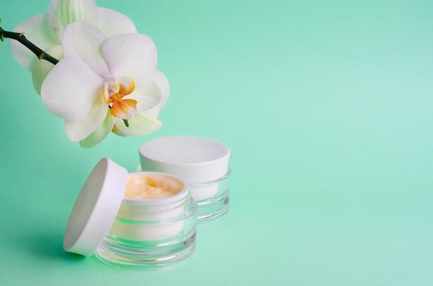 Prodotto cosmetico naturale antietà, antirughe, per freschezza, compattezza della pelle, crema, maschera per la casa, cura professionale del viso su sfondo blu. vuoto, modello, copia spazio