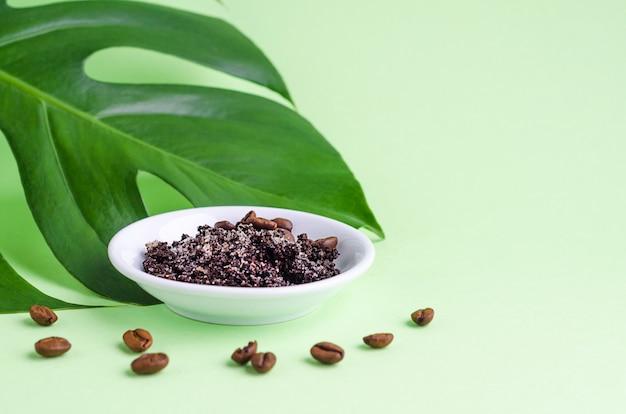 Prodotto cosmetico naturale per la cura della pelle. foglia di monstera e scrub con caffè macinato e fagioli per massaggio, esfoliazione