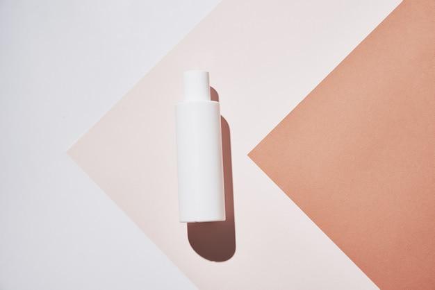 Bottiglia bianca del prodotto cosmetico naturale su fondo pastello