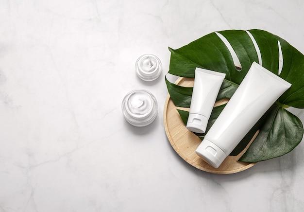 Prodotti cosmetici naturali con foglia su sfondo di marmo. lay piatto, copia dello spazio