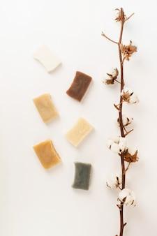 Cosmetici naturali. composizione con vari rami di sapone e cotone, cosmetici naturali su sfondo bianco, vista dall'alto piatta
