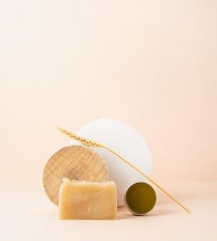 Cosmetici naturali. composizione artistica creativa con sapone e balsamo, cosmetici naturali su fondo beige con spazio copia