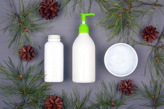 Cosmetici naturali su uno sfondo grigio con rami di abete e coni, copia spazio. bellezza del corpo e cura del viso.
