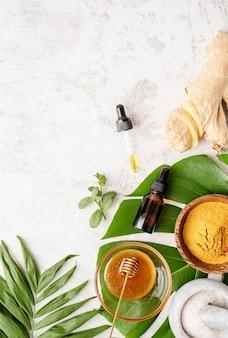 Ingredienti cosmetici naturali per la cura della pelle, del corpo e dei capelli. bottiglie vista dall'alto con prodotto per il trattamento del viso, foglie tropicali