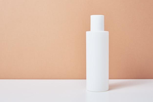 I cosmetici naturali deridono la bottiglia bianca di concetto del prodotto di bellezza su fondo pastello