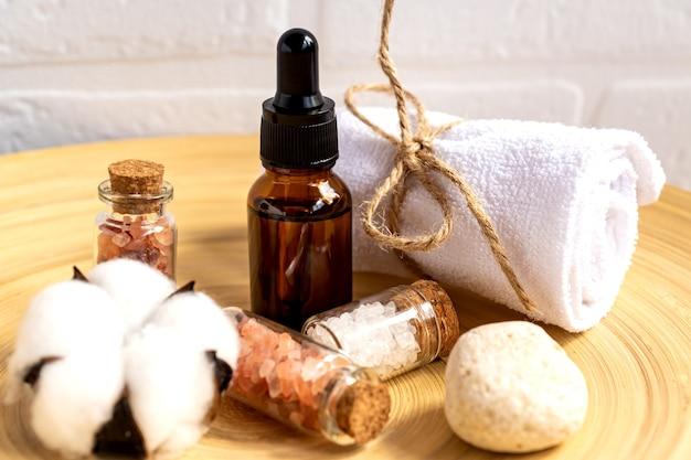 Set di cosmetici naturali in confezione ecologica in piatto di bambù con asciugamano in cotone. spa, prodotti di bellezza per il bagno
