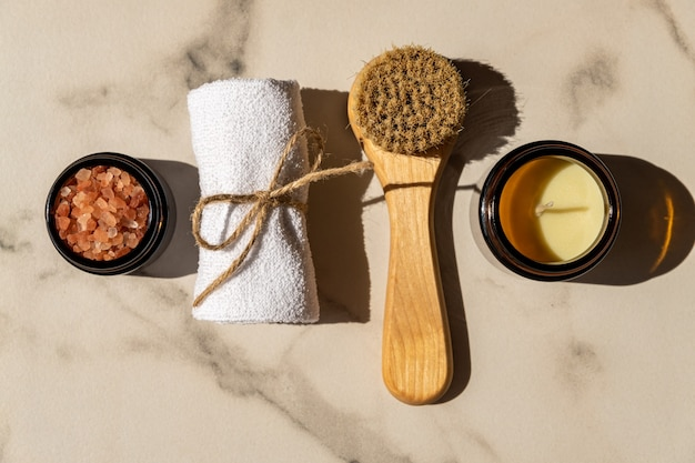 Cosmetici naturali in confezione ecologica su un tavolo di marmo con fiore in ctton e asciugamano. spa, prodotti di bellezza per il bagno