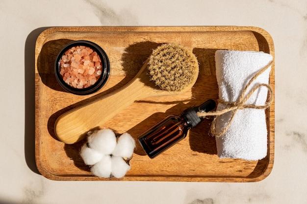 Set di cosmetici naturali in confezione ecologica in vassoio di legno con fiore in ctton e asciugamano. spa, prodotti di bellezza da bagno.