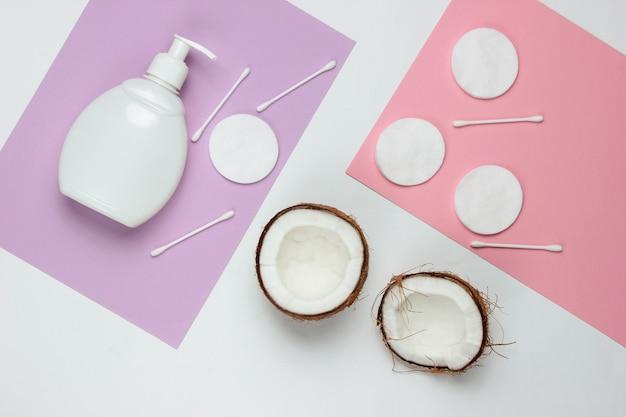 Cosmetici naturali, prodotti per la cura della pelle. noce di cocco, bottiglia di crema, accessori cosmetici su sfondo colorato.