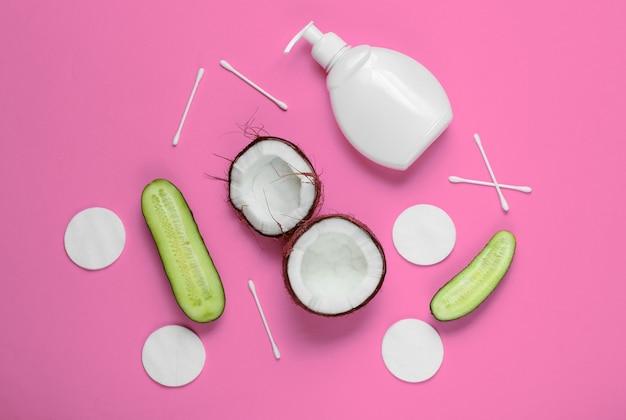 Cosmetici naturali, prodotti per la cura della pelle. noce di cocco, cetrioli, bottiglia di crema, accessori cosmetici sul rosa