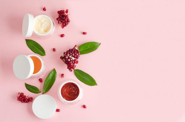 Cosmetici naturali con acidi aha di frutta, estratto di melograno su sfondo rosa. concetto di bellezza. vasetto con crema, maschera, scrub, peeling per la cura professionale della pelle del viso. banner, layout, copia spazio