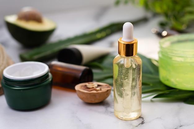 Cosmetici naturali con ingredienti a base di erbe, primi piani. una bottiglia di siero idratante o olio di aloe di avocado. idratante e concetto di cura della pelle.