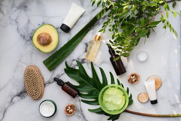 Cosmetici naturali con ingredienti a base di erbe, distesi. bottiglie di oli essenziali e un vasetto di crema idratante e foglie verdi su priorità bassa di marmo di pietra bianca