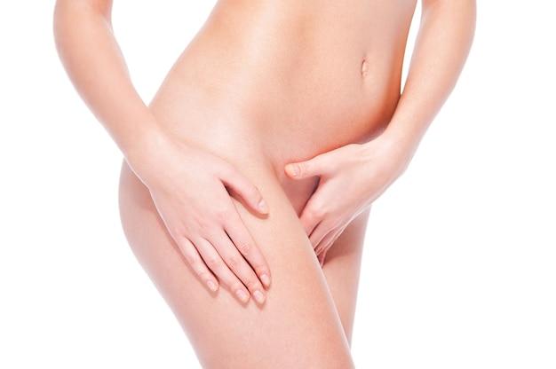 Curve naturali. primo piano di bella giovane donna senza camicia che tocca la sua gamba mentre stando contro il fondo bianco