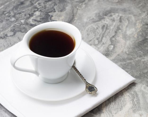 Cicoria bevanda naturale in una tazza bianca con un piattino su un tovagliolo bianco.