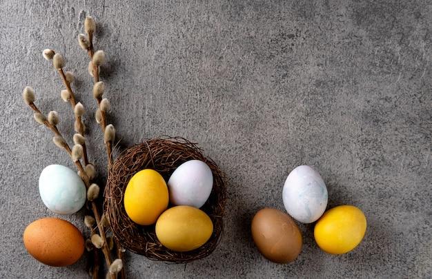 Uova di pasqua colorate naturali. composizione di pasqua su sfondo grigio cemento.