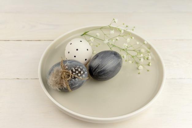 Uova di pasqua grigie tinte naturali in un piatto su fondo di legno rustico. punto di vista ad alto angolo.