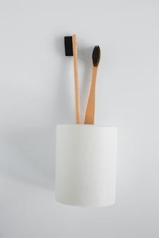 Spazzolino da denti naturale del bambù di eco nel supporto sulla vista superiore del fondo bianco
