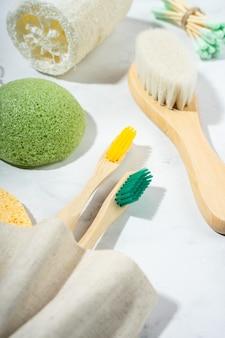 Accessori per il bagno eco naturale: pettine in legno, spazzolino da denti in bambù, spazzola per massaggi, bastoncini per le orecchie, spugna konjac su fondo marmo. prodotti etici a spreco zero. primo piano, piatto, vista dall'alto
