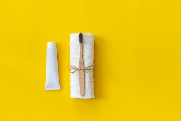 Spazzola di bambù naturale eco-friendly su asciugamano bianco e tubo di dentifricio.