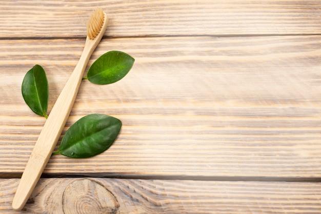 Spazzolino da denti di bambù ecologico naturale con foglie di albero verde su una superficie di legno