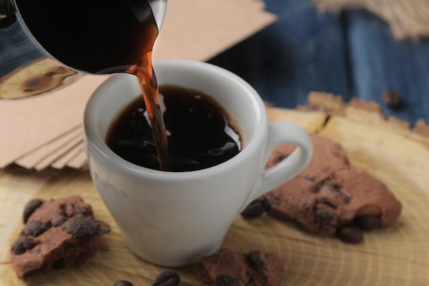 Il caffè espresso naturale viene versato con cezve in una tazza su un tavolo di legno blu