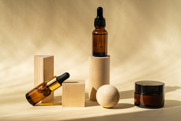 Olio essenziale naturale o siero in bottiglie di vetro marrone su podi di legno