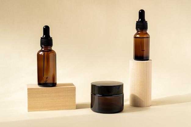 Olio essenziale naturale, siero e crema in una bottiglia di vetro marrone con una pipetta su un podio di legno