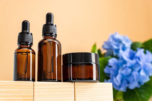 Olio essenziale naturale, siero e crema in bottiglie di vetro marrone su un podio di legno.