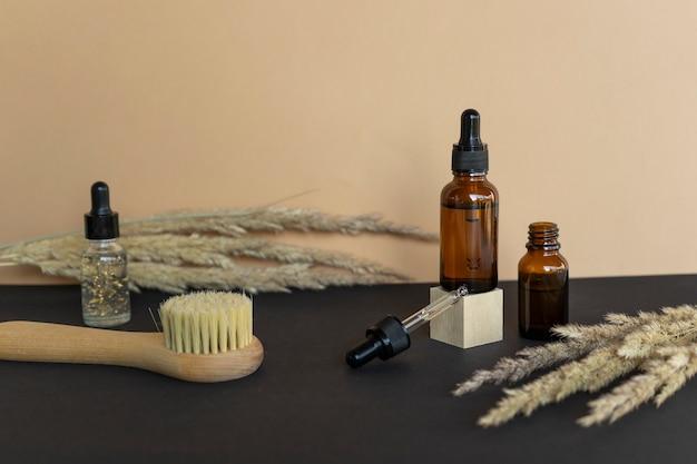 Oli essenziali naturali, siero in flaconi contagocce e una spazzola spa per il massaggio del viso. cosmetici naturali senza marchio