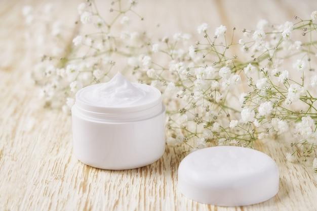 Crema viso o corpo naturale in un barattolo bianco su un tavolo di legno, messa a fuoco selettiva.