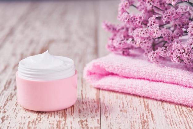 Prodotto per la cura della pelle del viso naturale in barattolo di plastica rosa con asciugamano sul tavolo bianco. vasetto di plastica rosa di crema per la pelle sensibile su un tavolo di legno.