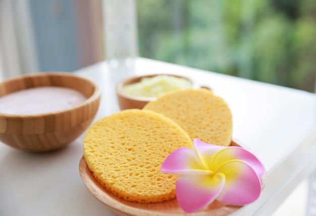 Spugna detergente viso in fibra naturale con bolle di schiuma di sapone. concetto di salute e bellezza.