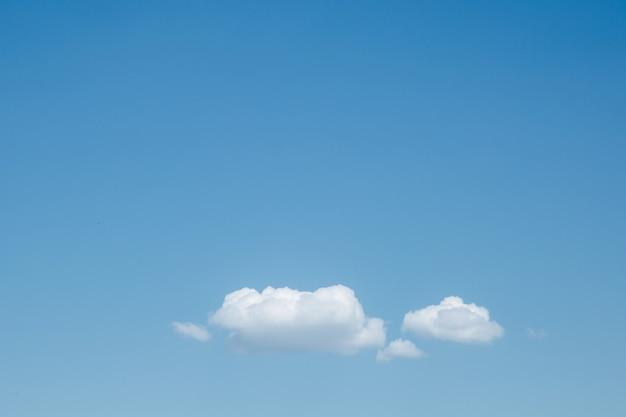 Nuvole bianche lanuginose naturali sullo spazio della copia del cielo blu