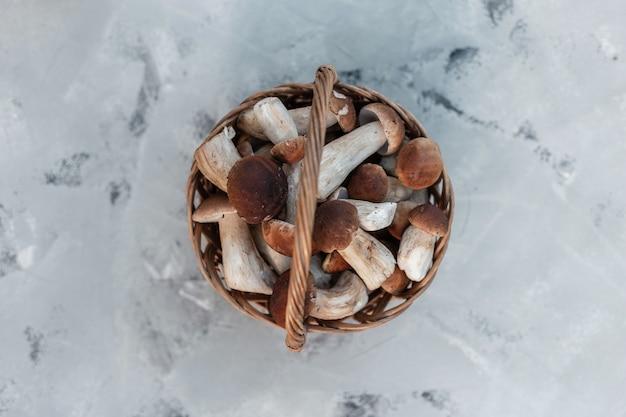 Funghi freschi naturali in un cesto di vimini su sfondo grigio, vista dall'alto