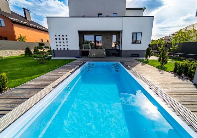 Giardino naturale con piscina d'acqua in casa lussuosa. giardino sullo sfondo. piscina con acqua pulita.