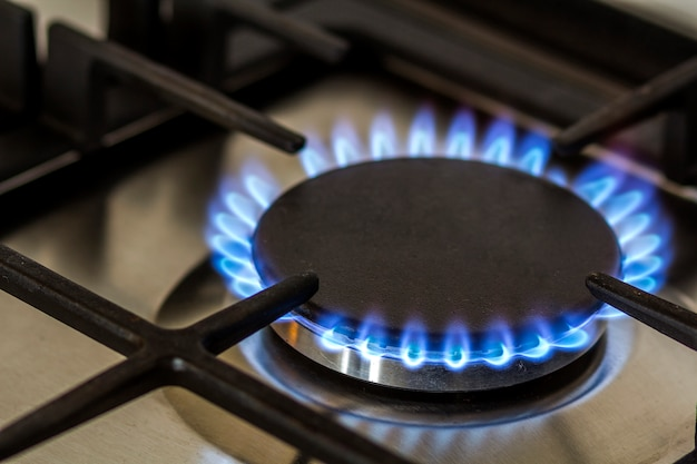 Gas naturale che brucia sul fornello a gas della cucina al buio.