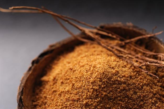 Zucchero di cocco granulato naturale nelle coperture della noce di cocco su un fondo nero