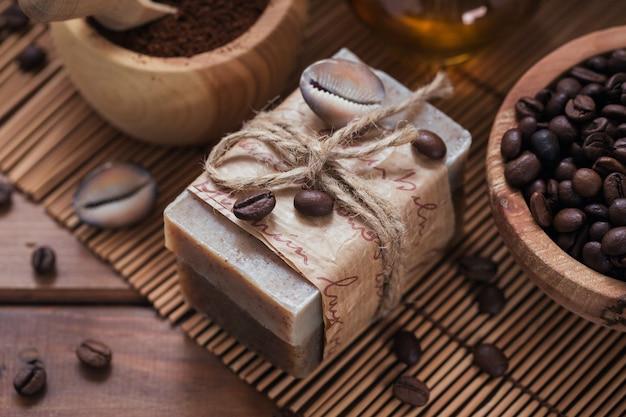 Sapone naturale fatto a mano, olio cosmetico aromatico, sale marino con chicchi di caffè su fondo di legno rustico. cura della pelle sana. concetto di sauna e spa. avvicinamento