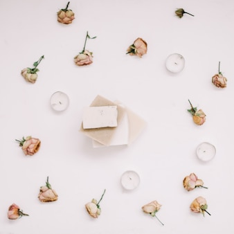 Sapone naturale fatto a mano in una cornice di fiori sul tavolo bianco