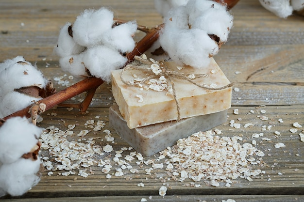 Sapone naturale fatto a mano, fiocchi d'avena e ramo di cotone su una superficie di legno
