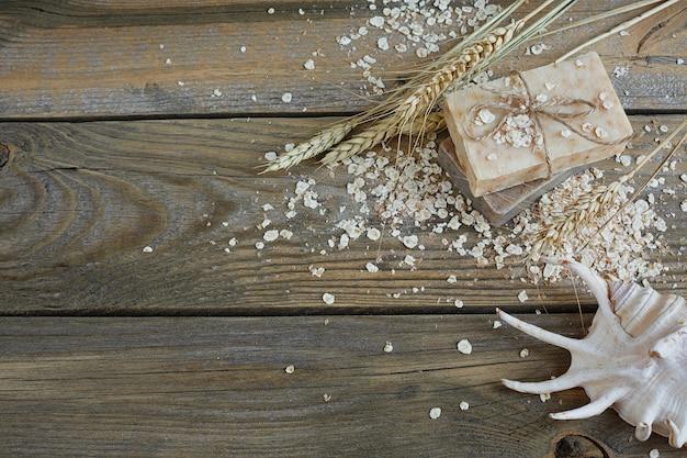 Sapone naturale fatto a mano, fiocchi d'avena e spighe di grano su una superficie di legno