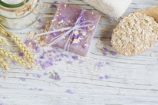 Sapone naturale fatto a mano, sale marino, asciugamano, fiocchi d'avena e spighe di grano su una superficie di legno bianca.