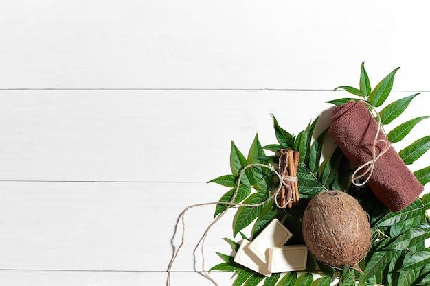 Saponi naturali fatti a mano con cannella, asciugamano marrone, cocco e foglie verdi su fondo di legno bianco. vista dall'alto. copia spazio. natura morta. disposizione piatta. set spa