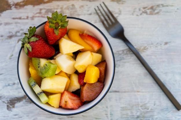 Insalata di frutta naturale e sana con arancia impostata in una ciotola su una superficie rustica.